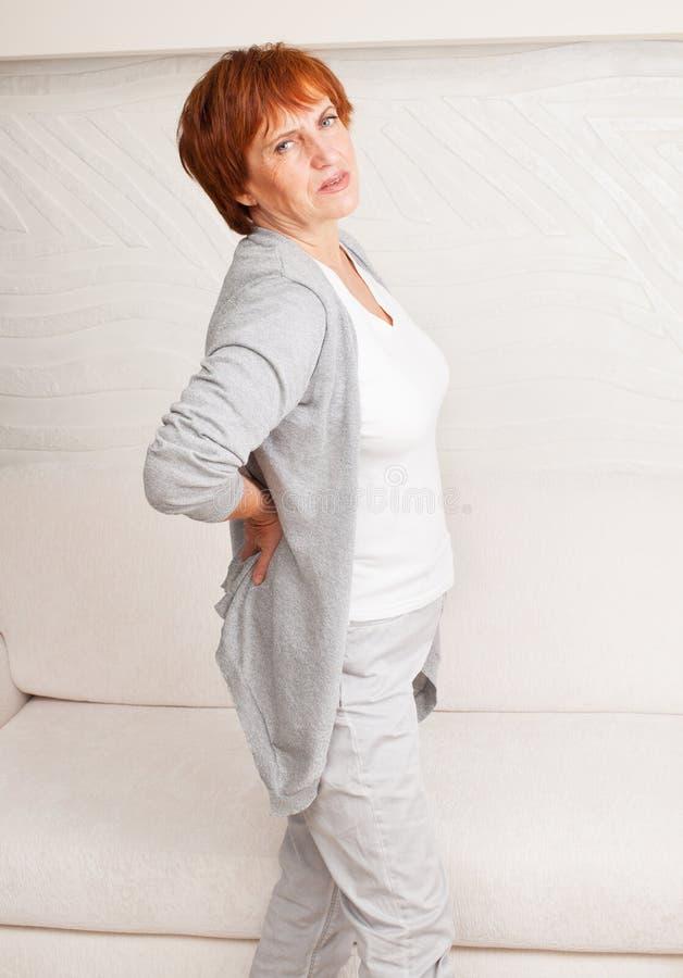 La femmina matura ha parte posteriore di dolore dentro fotografia stock