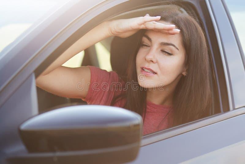 La femmina messa a fuoco attraente tiene la mano sulla fronte, esamina la distanza dalla finestra di automobile, prova a notare q immagini stock libere da diritti