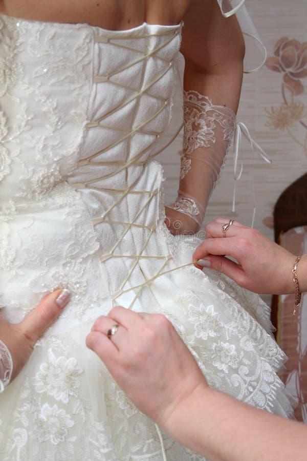 La femmina passa la sposa del corsetto immagini stock