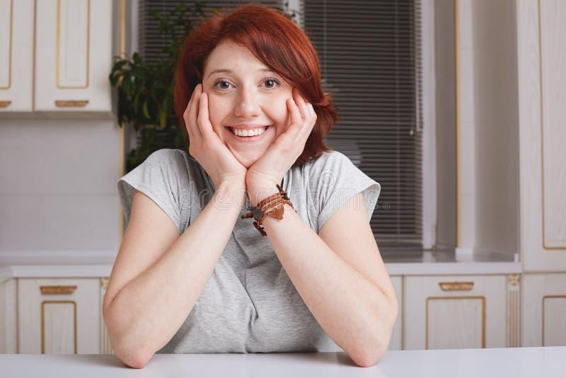 La femmina piacevole allegra con i brevi capelli dello zenzero esamina con l'espressione felice la macchina fotografica, tiene le immagini stock libere da diritti