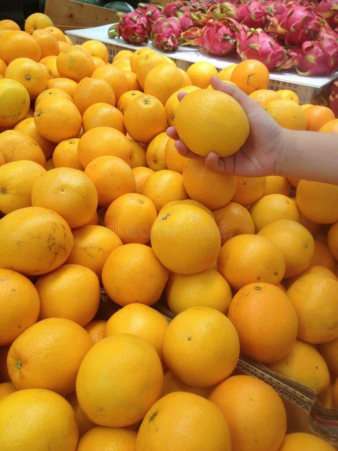 La femmina raccoglie a mano sull'arancia immagine stock