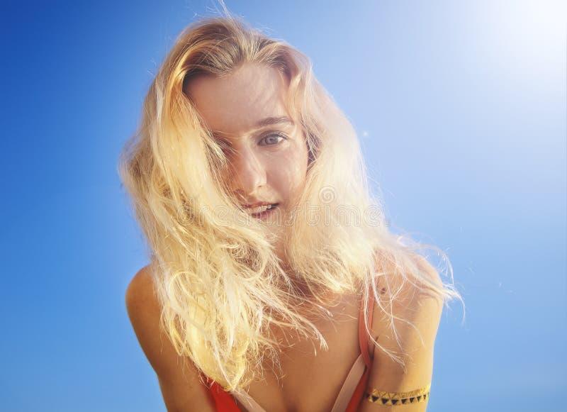 La femmina si è vestita in costume da bagno di corallo che sorride alla macchina fotografica Giorno, all'aperto Fine in su fotografie stock