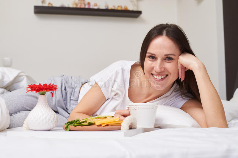 La femmina splendida si trova a letto godendo della prima colazione immagini stock libere da diritti