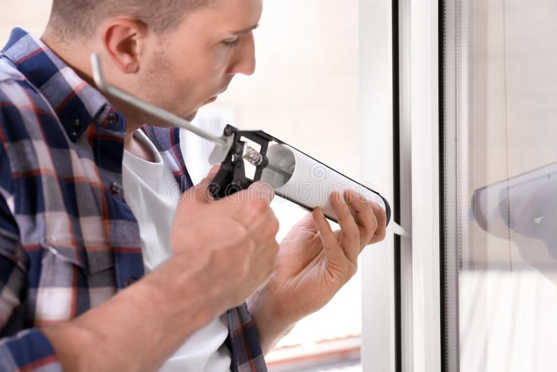 La fenêtre de cachetage de travailleur de la construction avec calfeutrent images stock