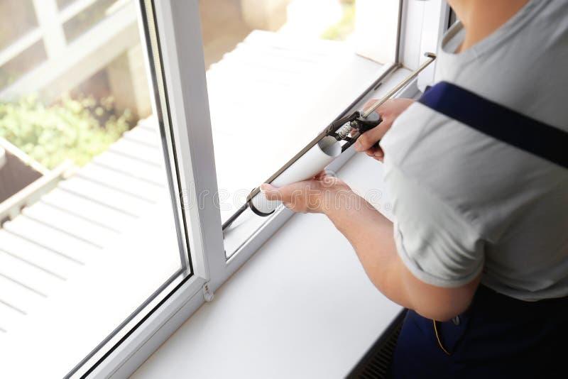 La fenêtre de cachetage de travailleur de la construction avec calfeutrent photographie stock libre de droits