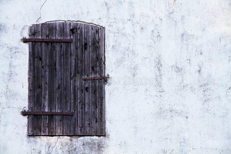 La fenêtre en bois fermée de brun foncé avec le métal rouillé s'articule sur un mur gris blanc sale image stock