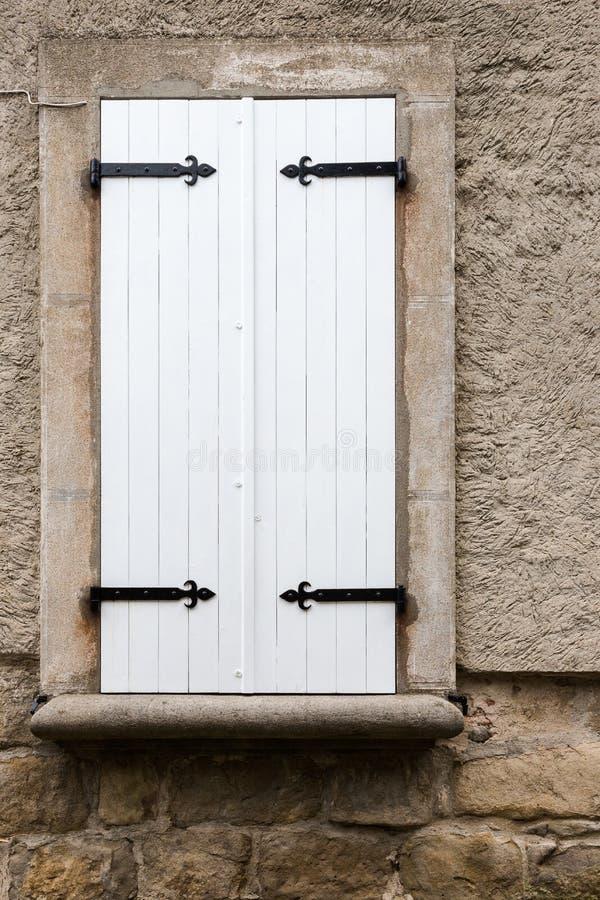 La fenêtre fermée en bois étroite blanche shutters avec des ornements en métal photos libres de droits