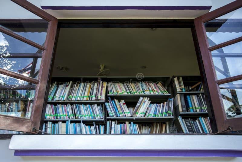 La fenêtre ouverte devant l'étagère avec beaucoup de livre contiennent la connaissance photo libre de droits