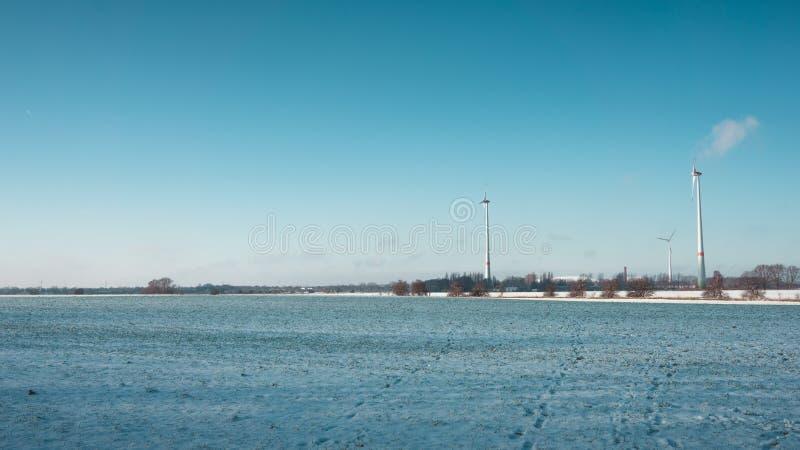 La ferme et la neige de turbine de vent ont couvert le champ de ferme photo libre de droits