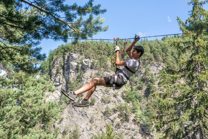 La fermeture éclair-doublure d'adolescent sur les cordes élevées courent, aventure, parc, grimpant à des arbres dans une forêt photographie stock libre de droits