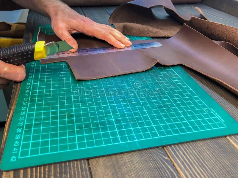 La fermeture d'un produit nouveau est faite, le maître coupe la peau photographie stock