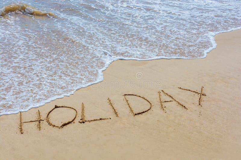 La festa di parola nella sabbia della spiaggia scritta con le onde di spuma fotografia stock