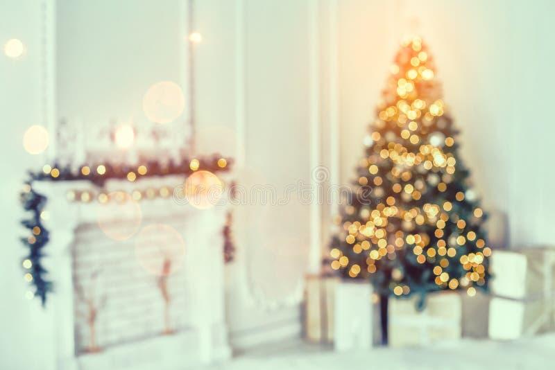 La festa ha decorato la stanza con l'albero di Natale e la decorazione, fondo con vago, scintillando, luce d'ardore fotografia stock