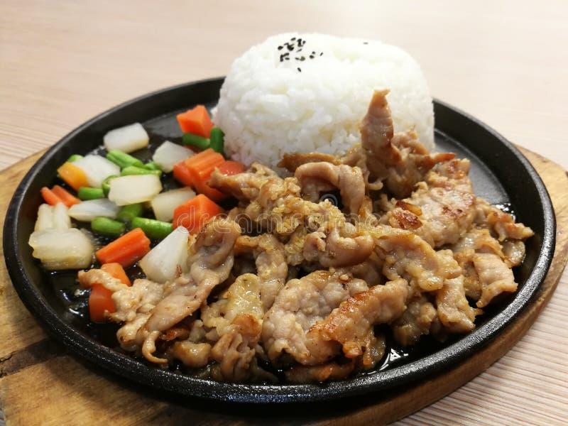 La fetta della carne di maiale della griglia sulla pentola calda del BBQ con il servire di verdure con riso, scalpore ha fritto l fotografia stock libera da diritti