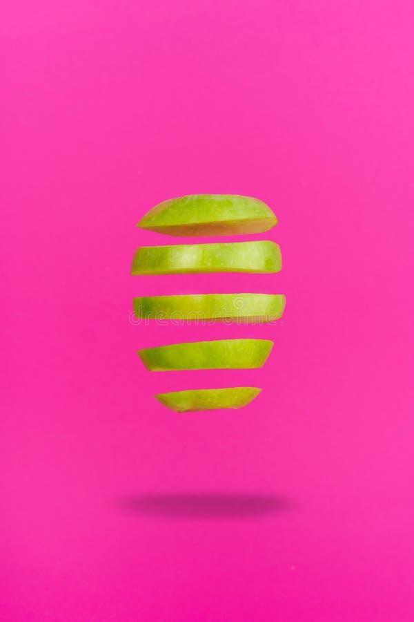 La fetta di Apple ha isolato la levitazione su fondo rosa immagine stock