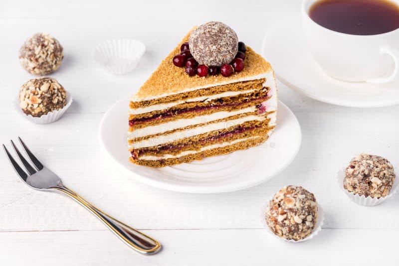 La fetta di miele casalingo saporito ed i mirtilli rossi agglutinano la tazza saporita del dessert del fondo bianco di tè immagine stock