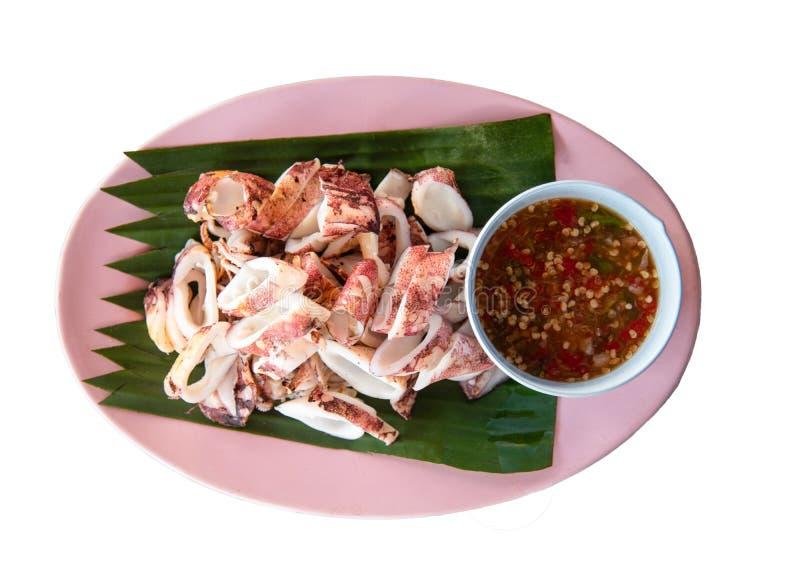 La fetta grigliata del calamaro sulla foglia della banana del piatto ha isolato il fondo bianco immagini stock