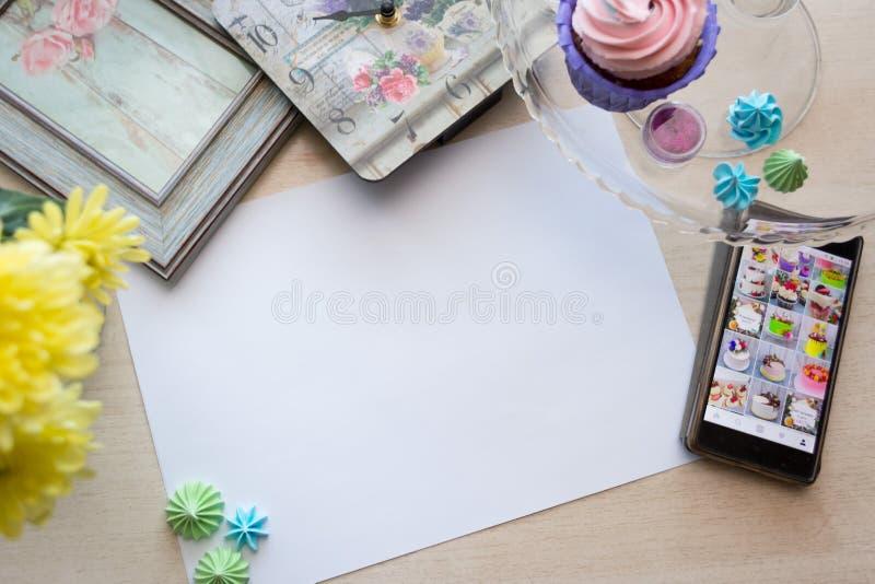 La feuille de papier blanche se trouve sur la texture de chêne blanc de table, autour des meringues de mensonge, horloge avec le  images libres de droits