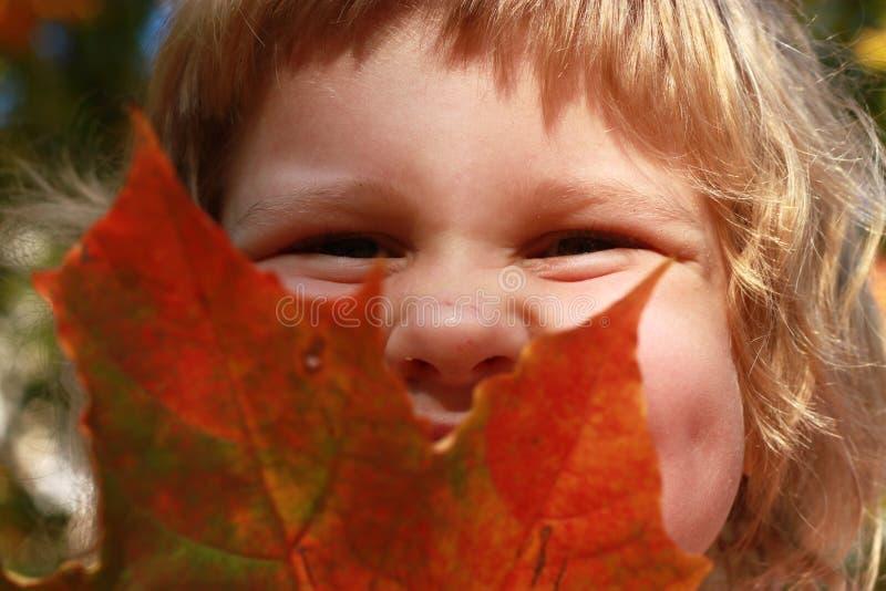 La feuille rouge riante de prise d'enfant, portrait automnal photo stock