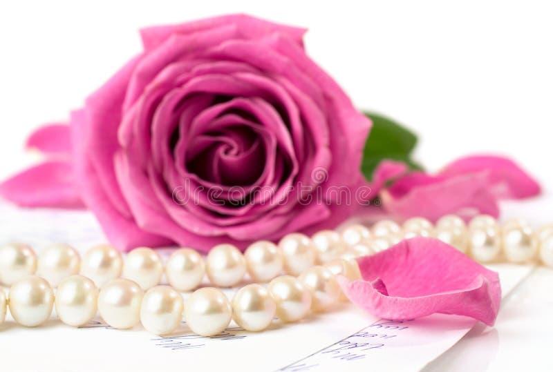 La ficelle des perles et d'un rose s'est levée images libres de droits