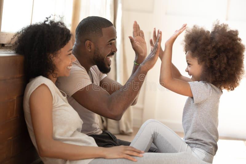 La figlia africana del bambino dà alto--cinque al papà che gioca con i genitori fotografie stock