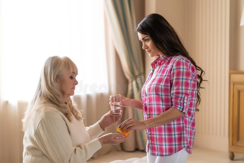 La figlia dà a sua madre senior le pillole e l'acqua fotografia stock