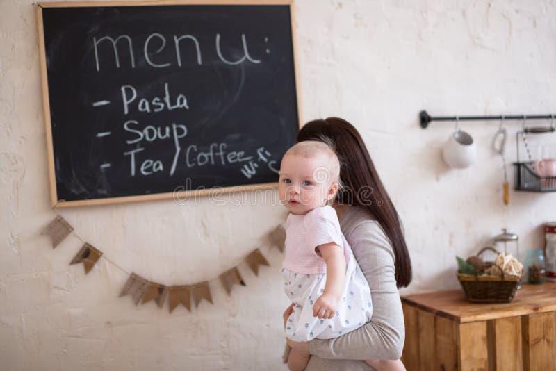 La figlia del bambino e della mamma che gioca la pianificazione del menu scrive al blackboa fotografia stock