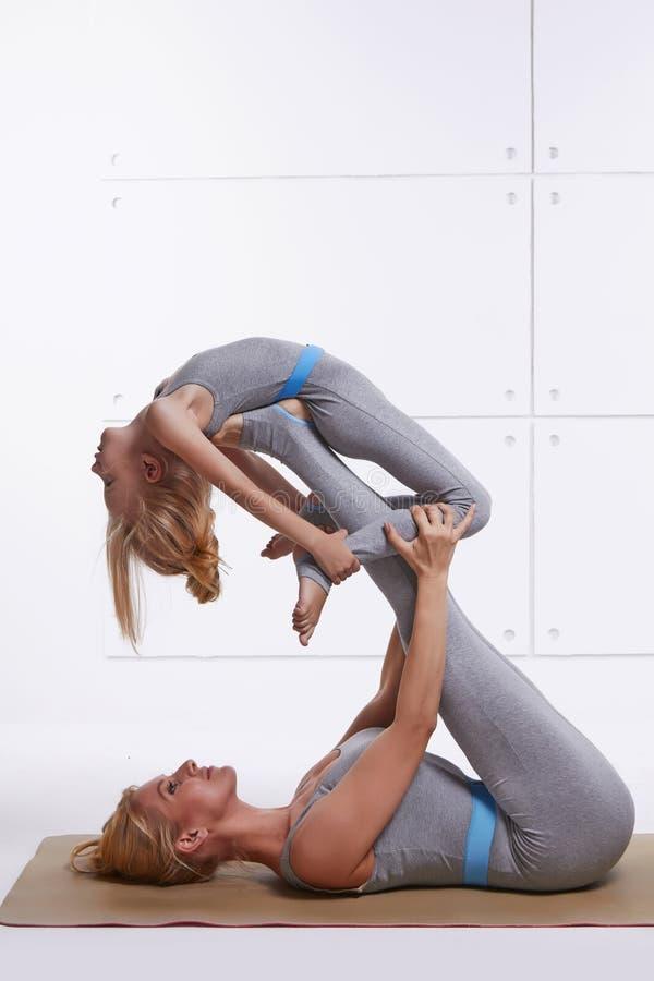 La figlia della madre che fa la palestra di forma fisica di esercizio di yoga che indossa gli stessi sport comodi della famiglia  fotografia stock libera da diritti