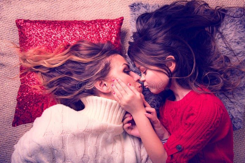 La figlia di amore con capelli lussuosi bacia sua madre, trovantesi sui cuscini si preoccupa, festa della Mamma, l'8 marzo, idill immagini stock