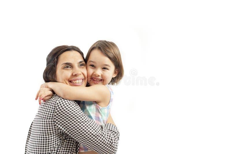 La figlia felice abbraccia sua madre, isolata su fondo bianco fotografia stock