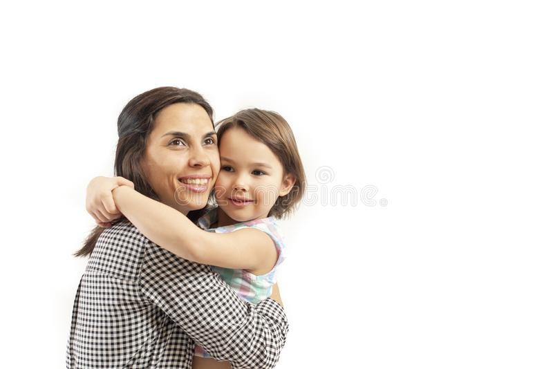 La figlia felice abbraccia sua madre, isolata su fondo bianco immagini stock