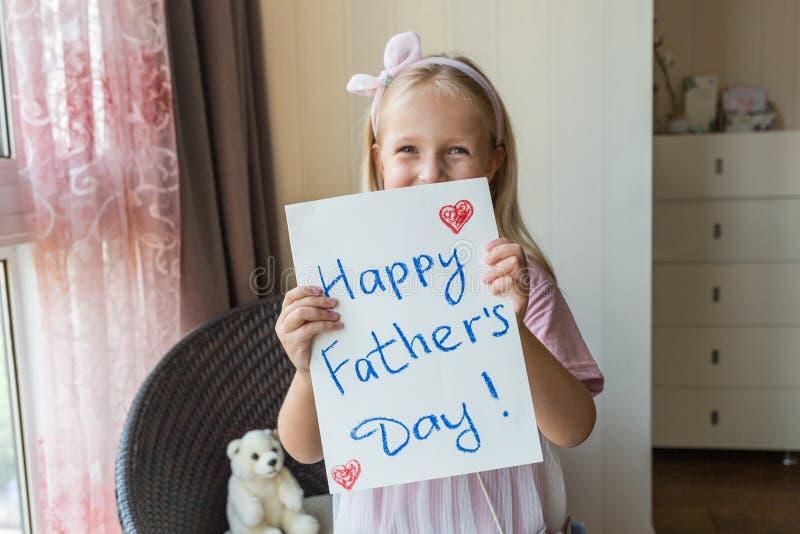 La figlia si congratula il pap? e le d? il regalo e la cartolina Concetto felice di giorno di padre immagine stock
