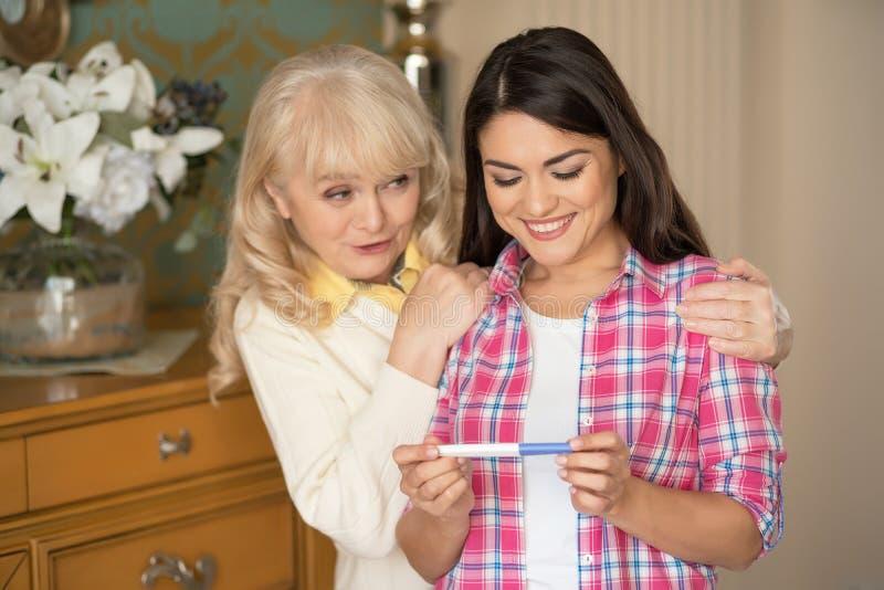 La figlia sorridente mostra il test di gravidanza a sua madre fotografie stock libere da diritti