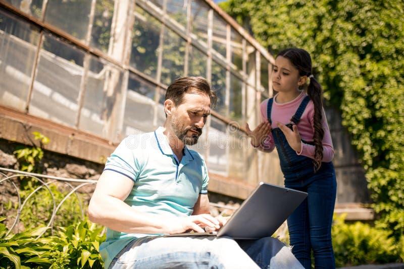 La figlia sta provando ad attirare l'attenzione del padre mentre stava l'aria aperta Padre Is Typing On il suo computer portatile immagine stock libera da diritti