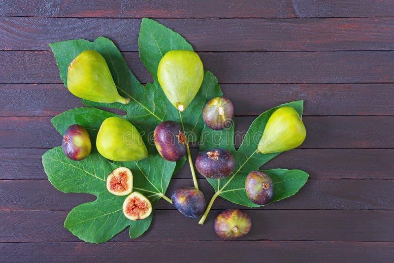 La figue mûre porte des fruits avec les feuilles vertes du figuier sur le fond en bois foncé Configuration plate photo stock