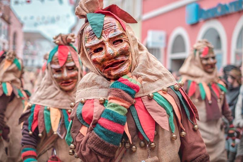 La figura carnaval amichevole in abito marrone, verde, rosso mostra il gesto di mano Carnevale in Germania del sud - foresta nera immagine stock