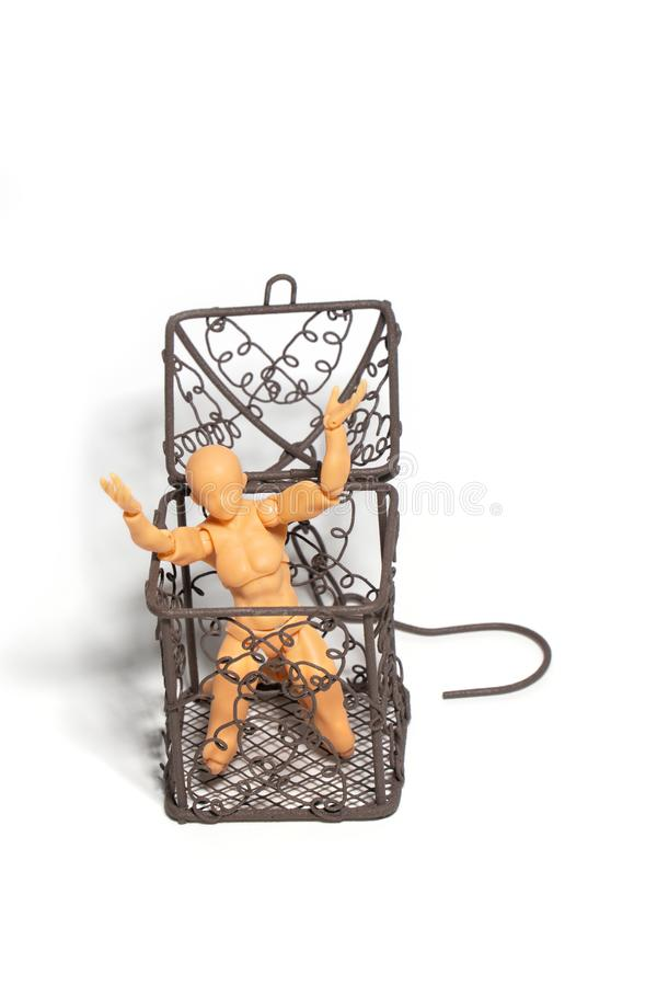 La figura de acción sentada y lleva a cabo dos manos sobre la cabeza en jaula de acero abierta en el fondo del aislante, concepto fotos de archivo