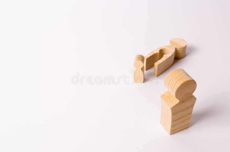 La figura de madera de un hombre mira el niño y a la madre de mentira El concepto de parto La muerte de la madre fotografía de archivo libre de regalías