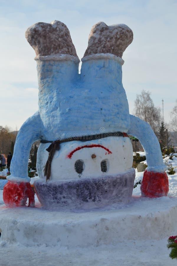 La figura de un héroe del cuento de hadas hecho de nieve se coloca al revés fotos de archivo