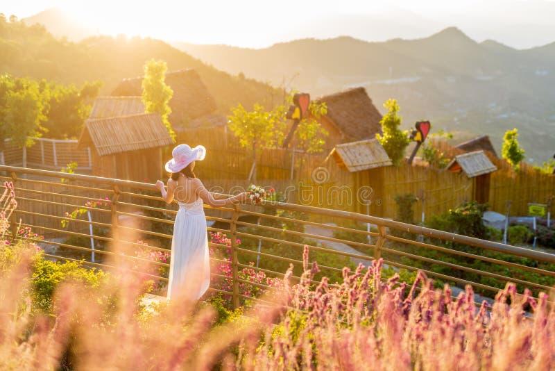 La figura de una mujer en un vestido blanco largo en la puesta del sol imagen de archivo