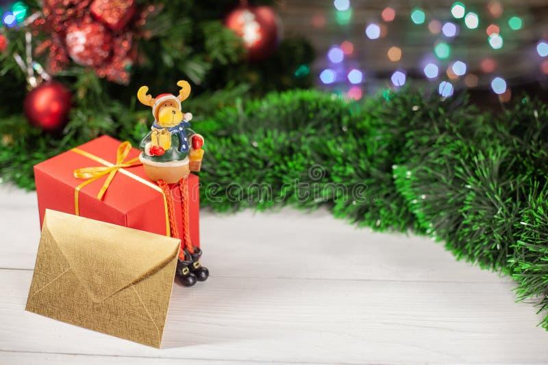 La figura dei cervi di Natale si siede su un regalo fotografia stock libera da diritti