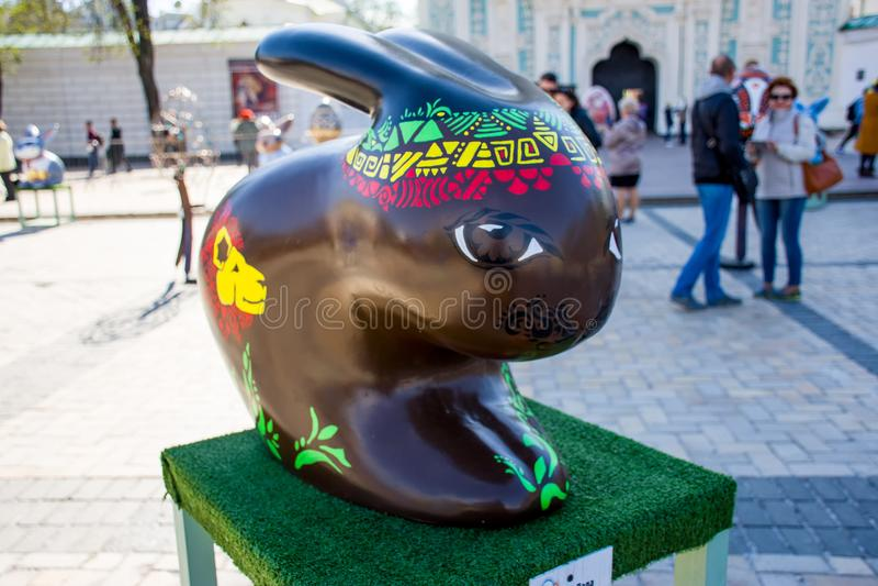 La figura del coniglietto di pasqua nel colore marrone con i motivi africani ed i modelli attinti il corpo nei colori verdi, gial immagine stock libera da diritti