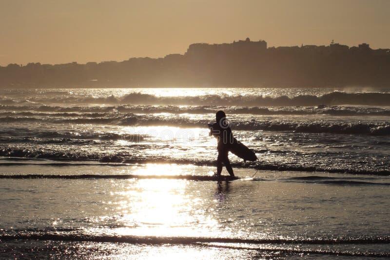 La figura del surfista a tempo di tramonto immagine stock