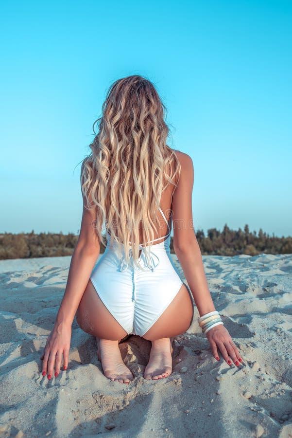 La figura delgada muchacha mira en el bañador blanco trasero, mujer hermosa del pelo largo, playa arenosa del verano que se sient imagen de archivo