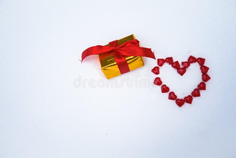La figura di un cuore presentato sulla neve di piccoli cuori rossi sulla neve sul San Valentino un regalo di sorpresa intorno Bac fotografia stock libera da diritti