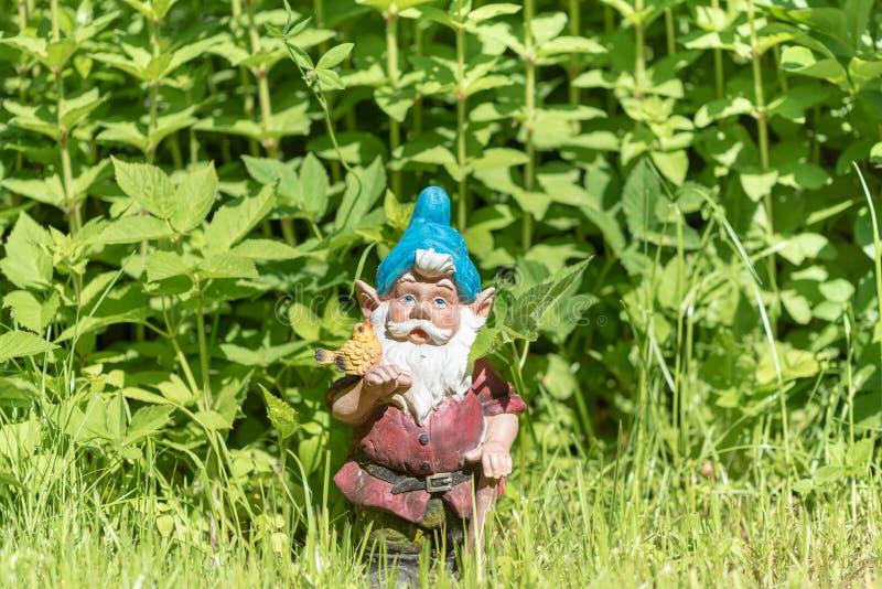 La figura di uno gnomo del giardino nell'erba verde Copi lo spazio Fuoco selettivo immagine stock libera da diritti