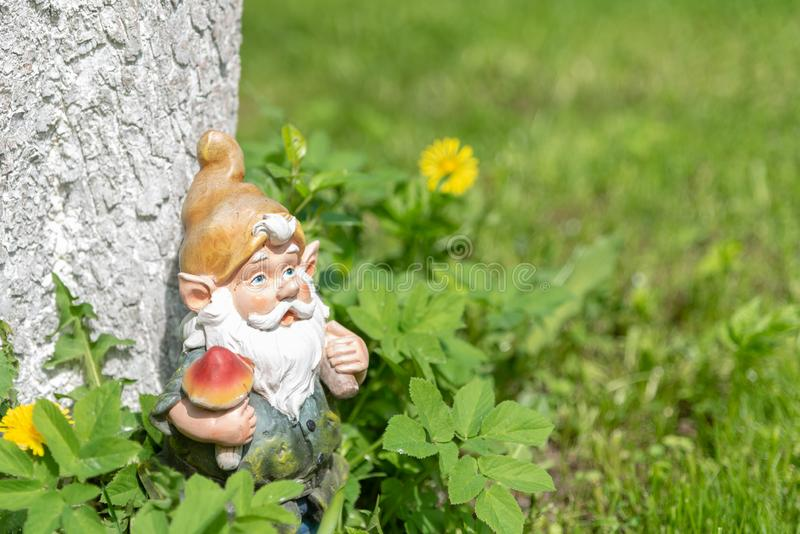 La figura di uno gnomo del giardino in un albero nell'erba verde Copi lo spazio immagini stock