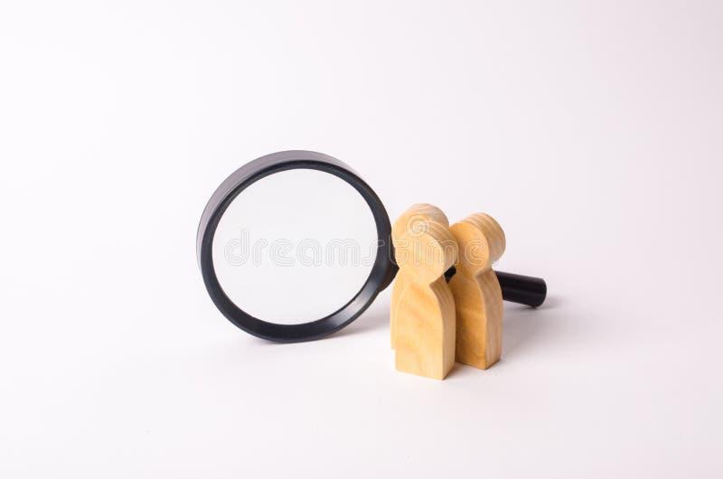 La figura humana de madera tres se coloca cerca de una lupa en un fondo blanco El concepto de la búsqueda para la gente y los tra imagen de archivo
