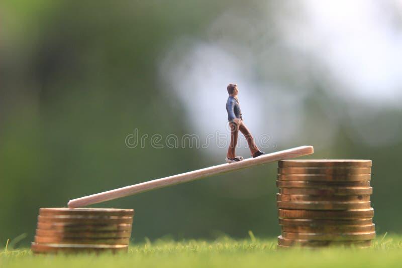 La figura miniatura bussinesman joven guarda el intentar conseguir una renta más alta que camina en la pila de moneda en la hierb imagenes de archivo