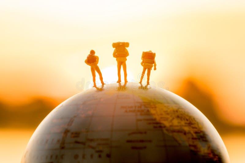 La figura miniatura gente hace excursionismo la situación en el globo con puesta del sol fotografía de archivo libre de regalías